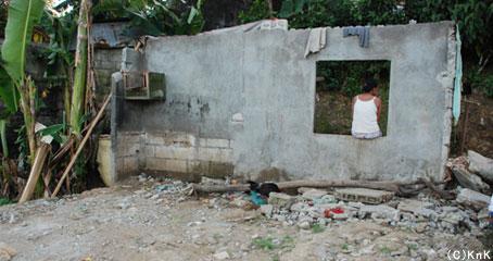 残された壁一枚にKnKが配布したビニールシートで屋根を作り家族4人が生活している。