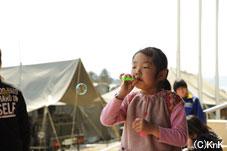 避難所となっている小学校に配られたシャボン玉で遊ぶ少女。