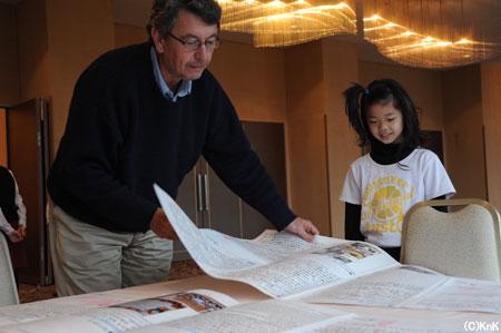 花巻の旅館で避難生活をおくっている少女に、 海外や全国からKnKに送られてきたメッセージを見せる事務局長