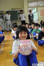 ロクシタン・ジャパンからもらったお菓子を 手にする釜石市立栗林小学校の児童