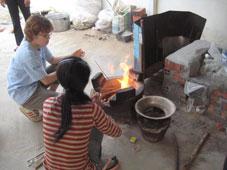 染めのために、屋外で薪割り、火起こし。  奥はお手伝いの大沼文香さん (2007年友情のレポーター)。  元気いっぱいの20歳!!