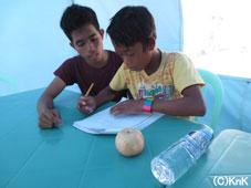アクティビティ終了後も残って一生懸命学習する子どもと励ましながらサポートするスタッフ(タナワン)