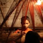 サリー工場で見習いをする少年。職人が帰宅後にからまった糸くずを取る。(ダッカ)