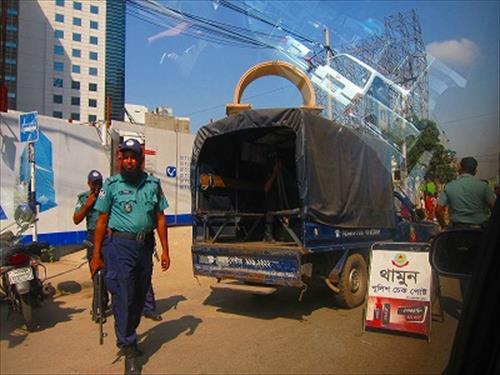 銃とトランシーバーを携えた警官たち。