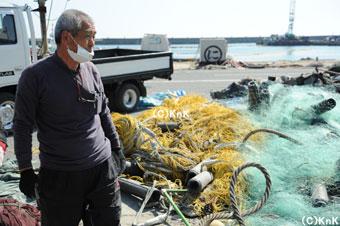 「嘆いていてもはじまらねぇ。今できることするしかないんだ。」と、 絡まった網で使えるものを仕分けしている漁師の方。
