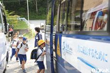 スクールバスへ乗り込む子どもたち