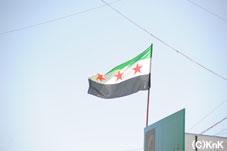 難民キャンプにそびえる  シリアの自由を求める三ツ星の旗
