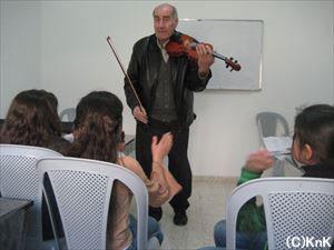 子どもの前でバイオリンを演奏