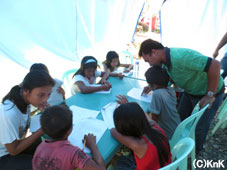 算数の問題に一緒に取り組むスタッフと子どもたち (タナワン)