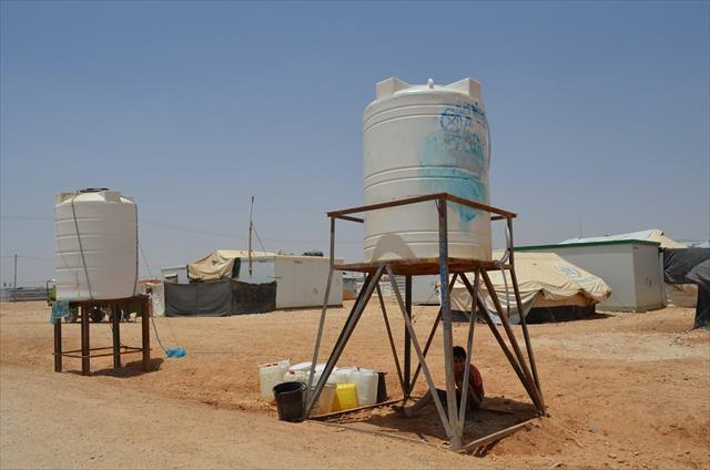 ラマダン中の昼間、タンクの下で涼む子ども。キャンプ内には日影が少なく、夏は歩くだけでとても暑い。