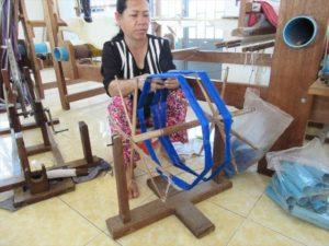 生地を織るための絹糸を準備する女性(KnKカンボジア))
